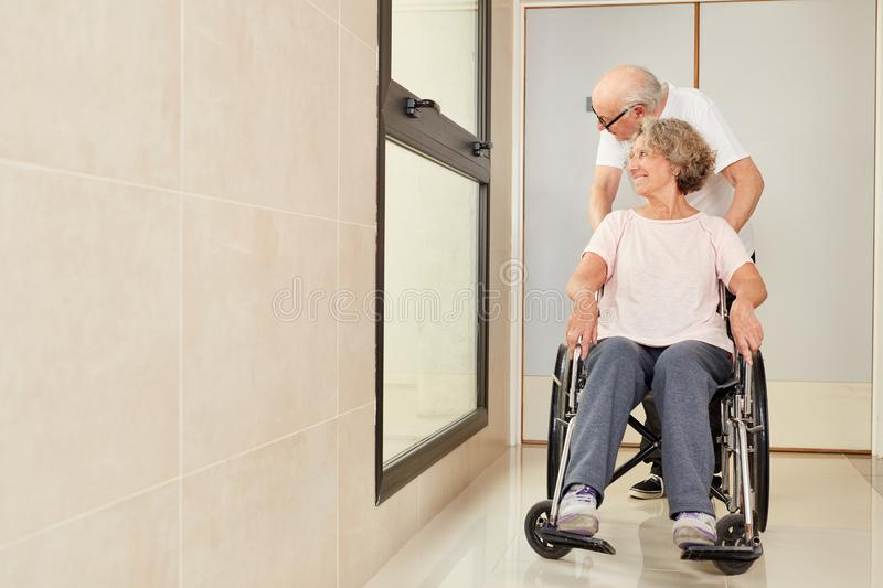 Man pushes his wife in a wheelchair stock photography