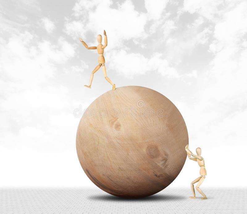Man pushes a huge wooden ball and another tries not to fall from it stock images