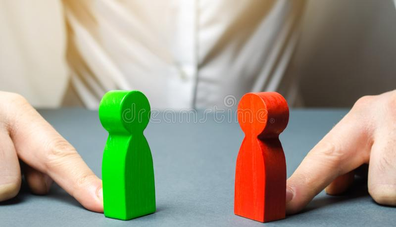 The man pushes the red and green figures to each other. The search for a compromise, mediation in negotiations. conflict. Of interest Analysis, situation stock photo
