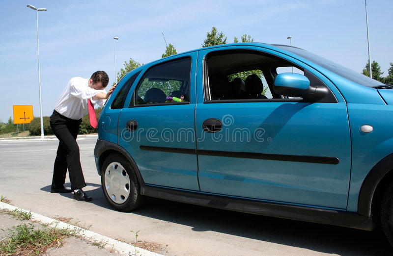 Man pushing a car stock photography