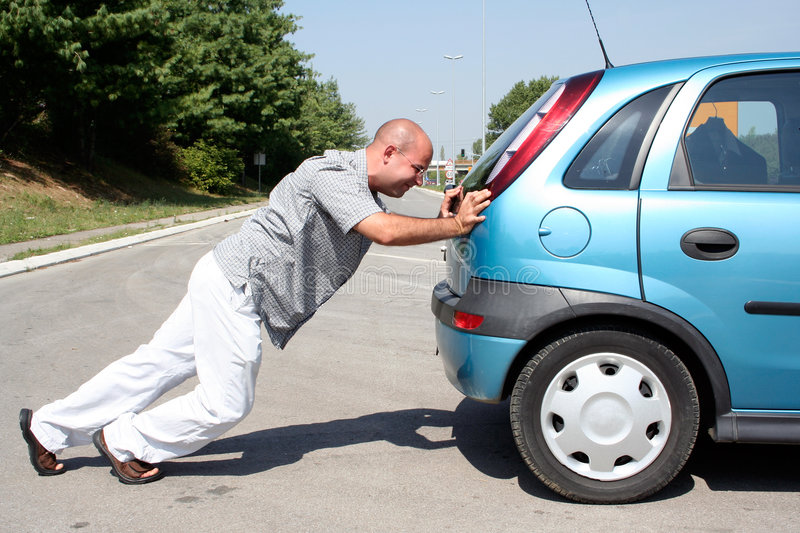 Man pushing a car stock images