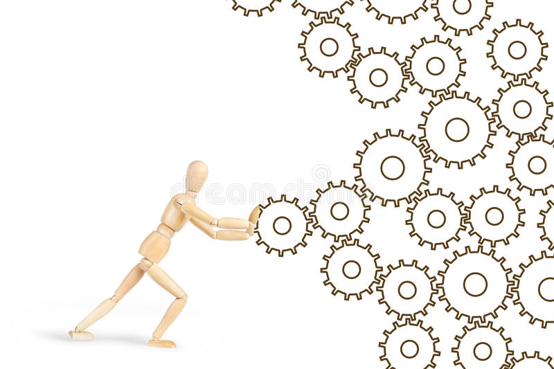 Man pushing the cogwheels to make mechanism working. Abstract image with a wooden puppet royalty free stock image