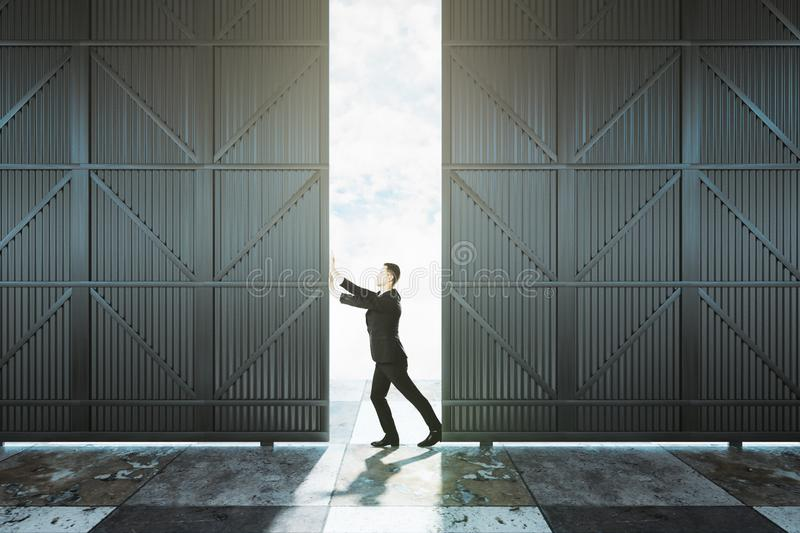 Man pushing hangar door. Open. Warehouse and storage concept royalty free stock photo