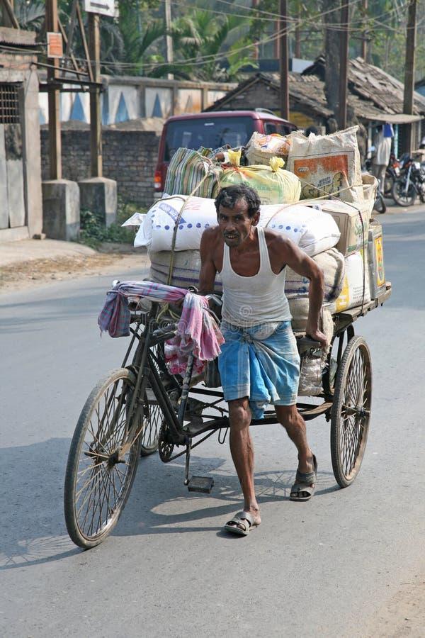 Man pushing heavily loaded cycle rickshaw royalty free stock photos