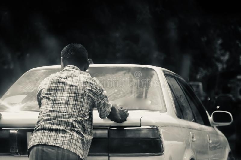 Man pushing an inactive cars on a city streets in Dhaka. Unique stock photo stock photo