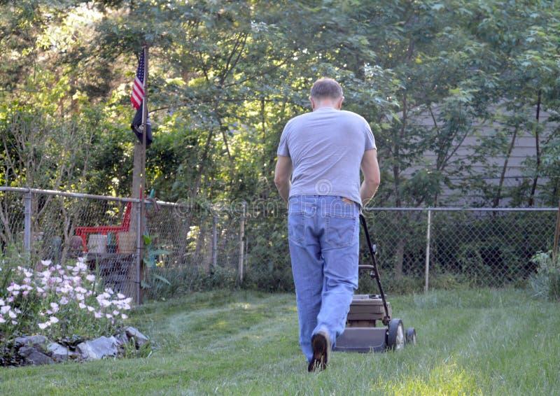 Man pushing lawn mower stock photo