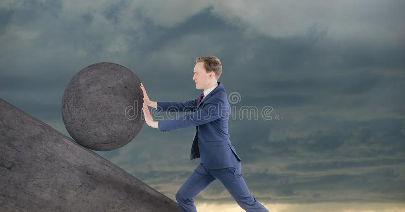Man pushing rolling round rock royalty free stock photos