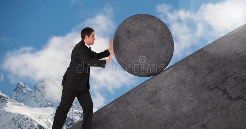 Man pushing rolling round rock royalty free stock image