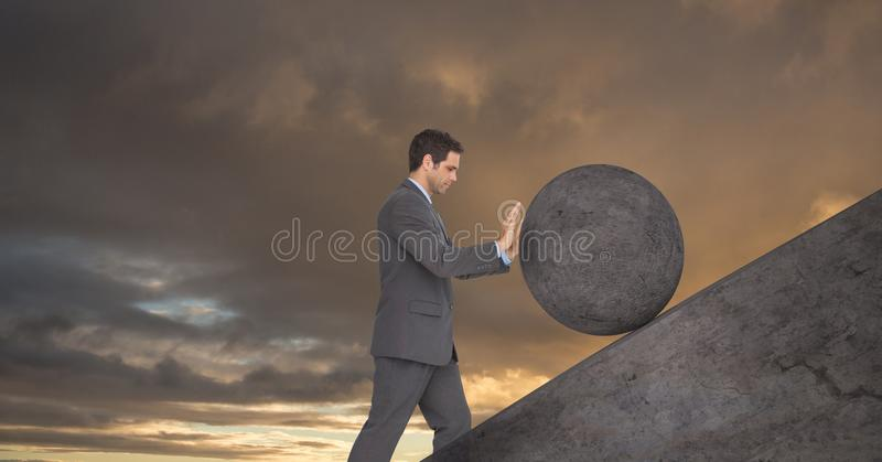 Man pushing rolling round rock royalty free stock photography