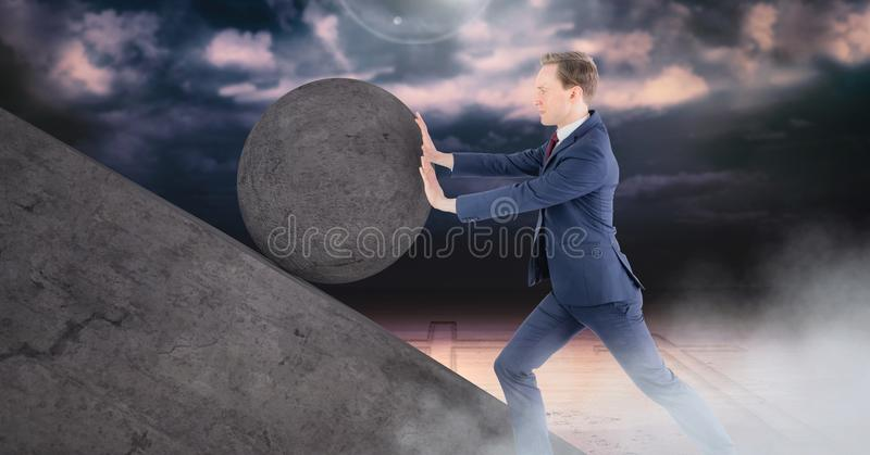 Man pushing rolling round rock stock photo
