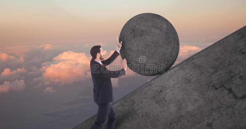 Man pushing rolling round rock royalty free stock photo