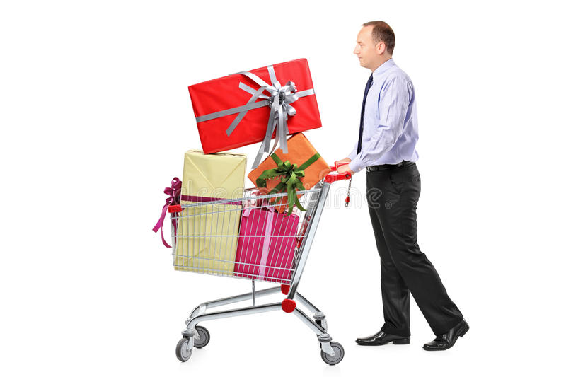Man pushing a shopping cart full with presents. On white background stock images