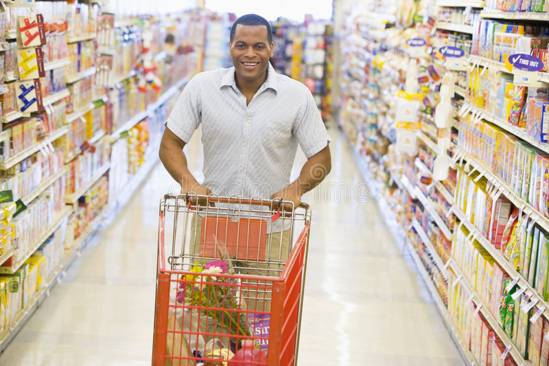 Man pushing trolley along supermarket aisle stock photo