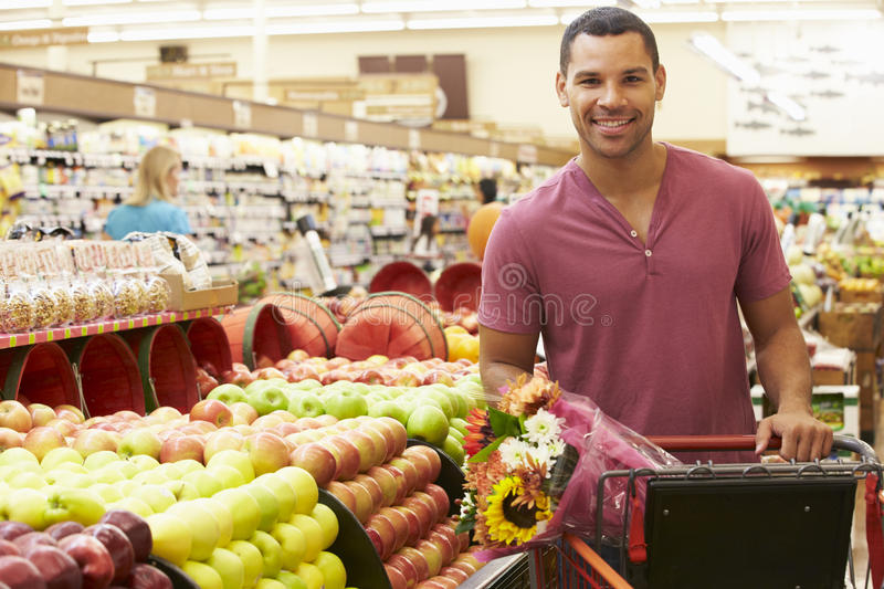 Man Pushing Trolley By Fruit Counter In Supermarket stock image