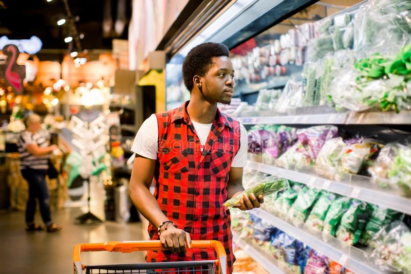 Man Pushing Trolley By Produce Counter In Supermarket royalty free stock image