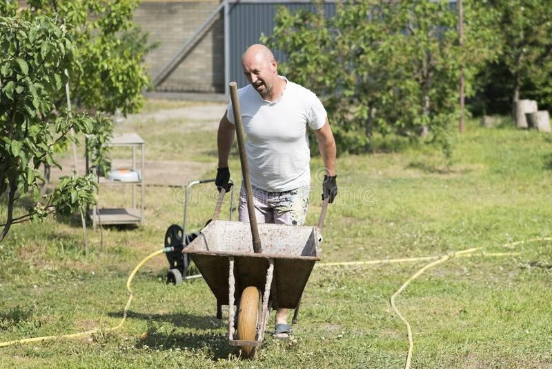 man pushing wheelbarrow. Young man pushing a wheelbarrow on the farm royalty free stock photos