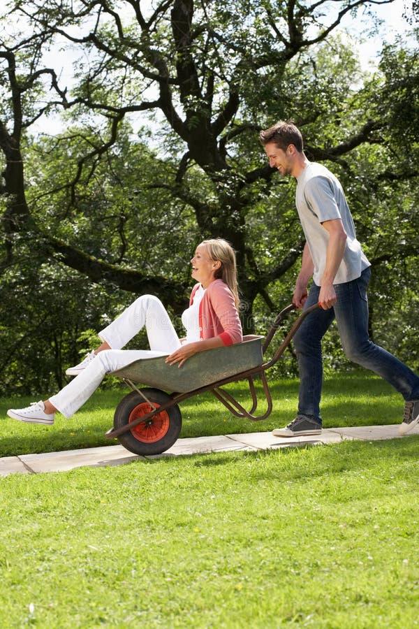 Man Pushing Woman In Wheelbarrow stock photos