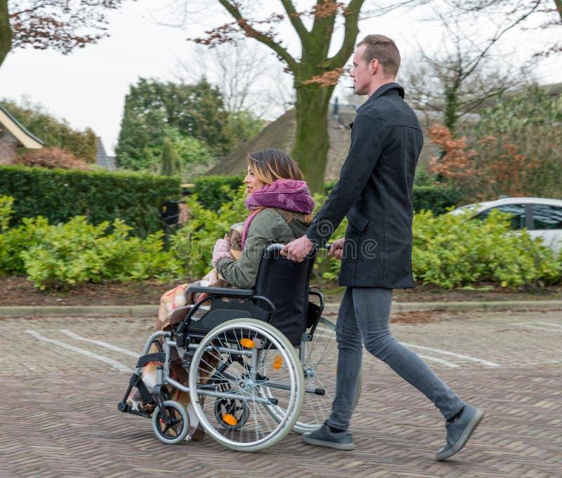 Man Pushing A Woman In A Wheelchair At A Car Park Stock