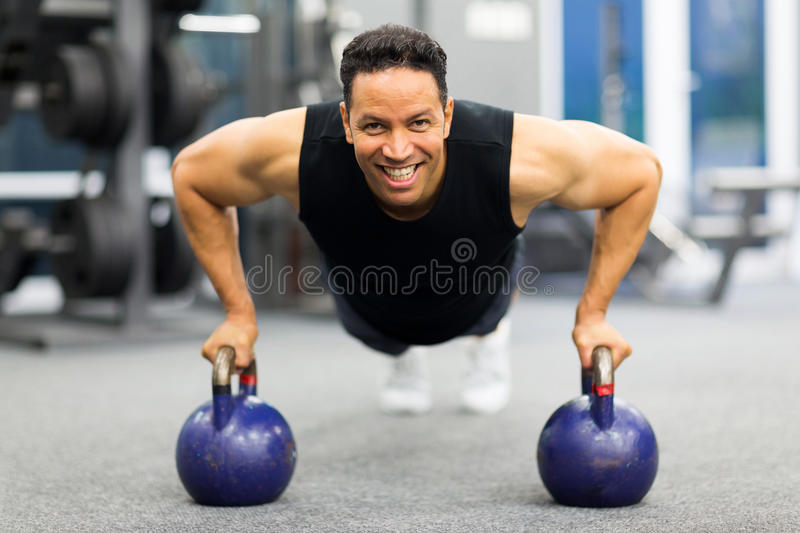 Man pushup kettle bell. Healthy man doing pushup exercise with kettle bell in gym stock image