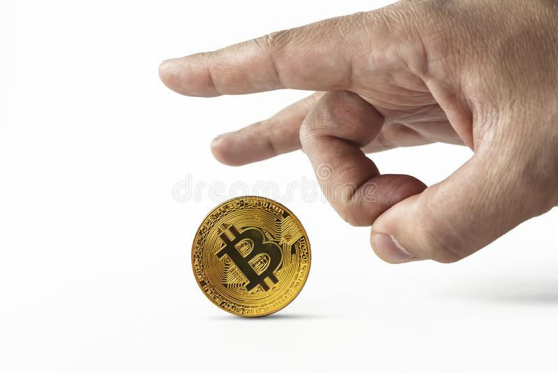 Man put bitcoin on edge and pulls it away kicking with index finger. Depreciation of virtual money bitcoin. Concept of. Depreciation of cryptocurrency royalty free stock photos