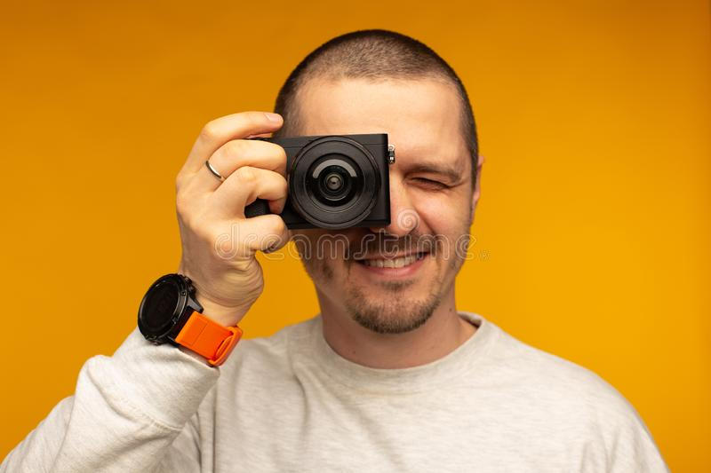 Man put camera to his eye. Photographer or videographer stock image