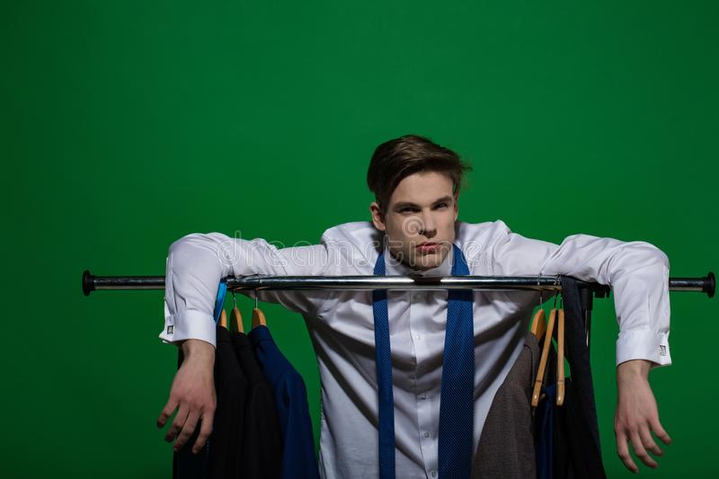 Man put hands on rack with clothes in wardrobe. Businessman in white shirt, blue tie on green background. Business fashion, style concept. Clothing, dressing stock image