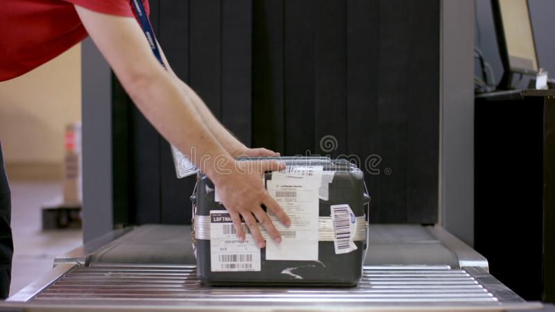 Man put Luggage at check-in counter at airport. X-ray machine at the airport check-in counter. Security check of hand stock image
