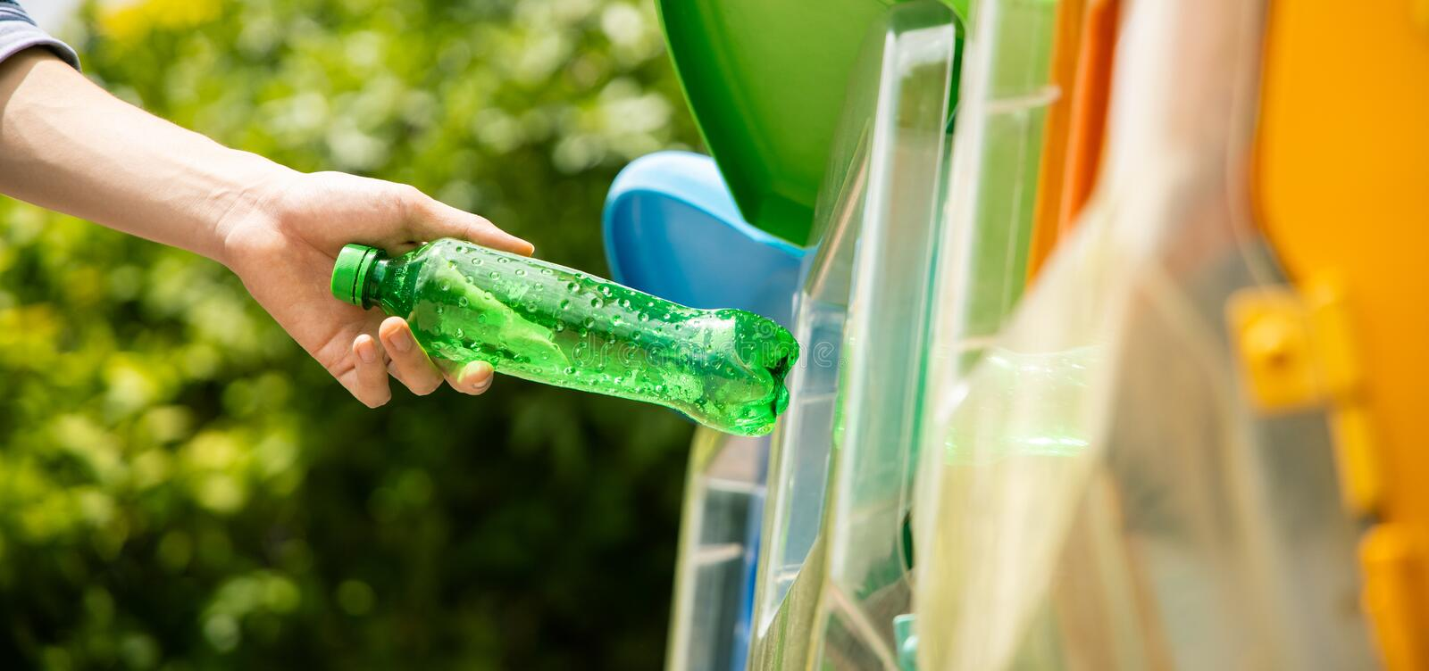 Man put plastic bottle into recycle bin in park. Close up shot, hand putting green empty plastic bottle into recycle bin. Panorama ratio stock photo