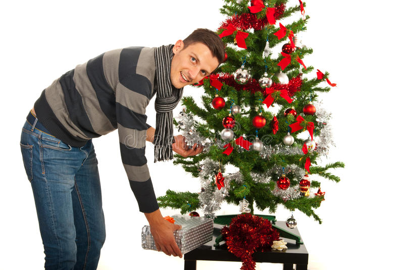 Man put present under tree. Man put a present under Christmas tree on table royalty free stock photos