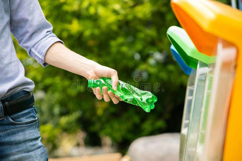 Man put twisted plastic bottle into recycle bin in park. Male hand putting twisted empty plastic drinking water bottle into recycle bin stock photos