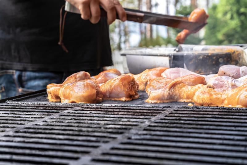 Man puts chicken on the grill to prepare a family dinner in the courtyard of the house, on a sunny summer day. Barbecue in the. Man puts chicken on the grill to stock image