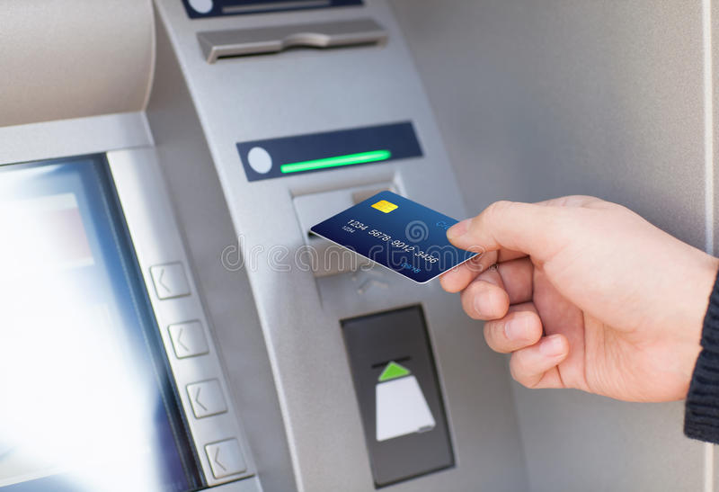 Man puts credit card into ATM. Man hand puts credit card into ATM stock photo