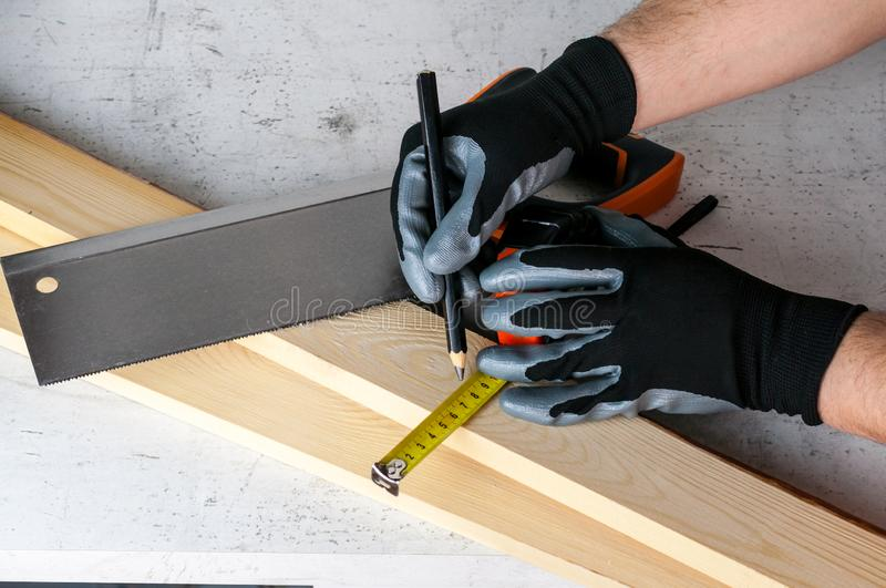 A man puts marks on the wooden bars with a pencil for further work with a saw. Diy at home concept.  stock photos