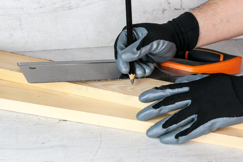 A man puts marks on the wooden bars with a pencil for further work with a saw. Diy at home concept.  stock image