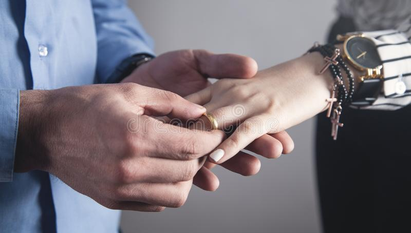 Man puts a ring on the hand of a girl royalty free stock image