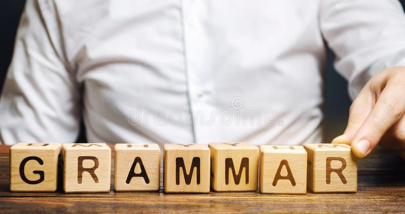 A man puts wooden blocks with the word Grammar. Set of structural rules governing the composition of clauses, phrases and words in. A natural language stock image