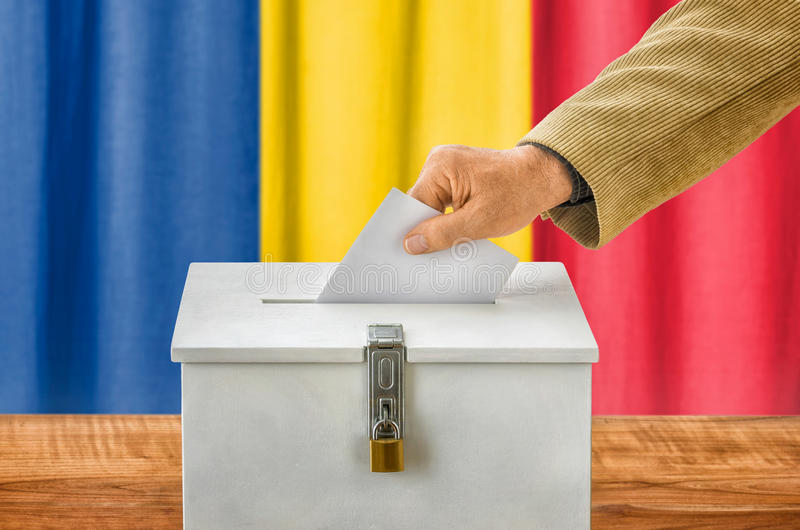 Man putting a ballot into a voting box - Romania stock images