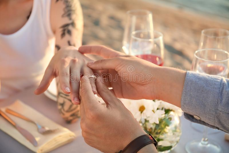 Man putting beautiful engagement ring on hand of his beloved outdoors, closeup royalty free stock image