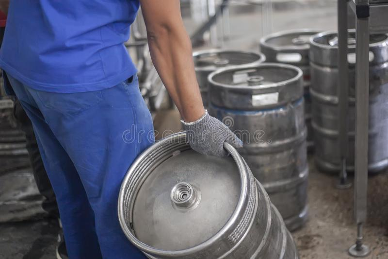 Man putting beer kegs on the production line in the factory. Process of beer production royalty free stock image