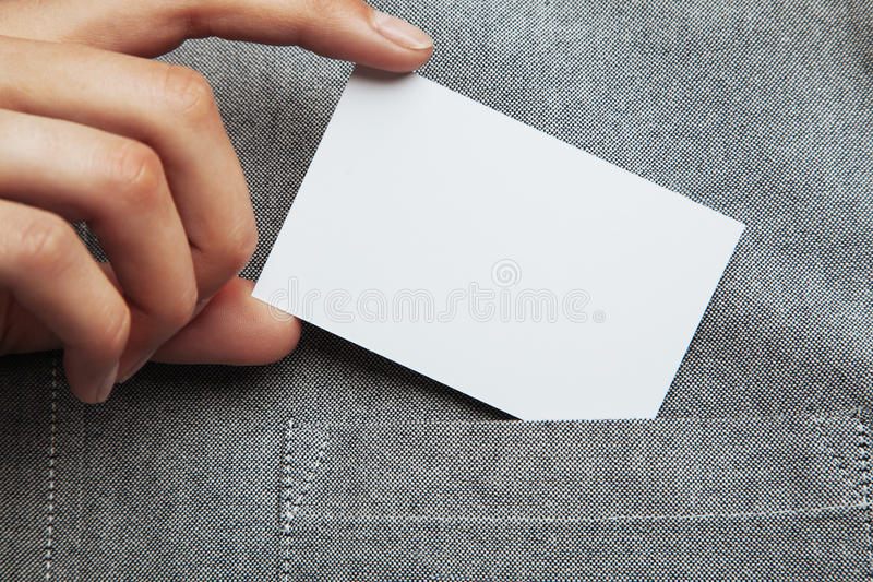 Man putting blank business card in his pocket of shirt. Closeup of man putting blank business card in his pocket of shirt. Horizontal stock images