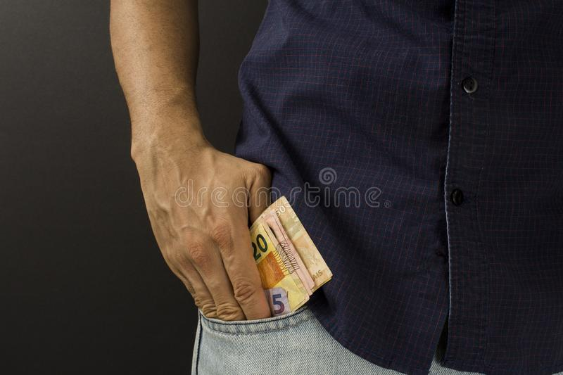 Man putting brazilian money inside the pocket royalty free stock photo