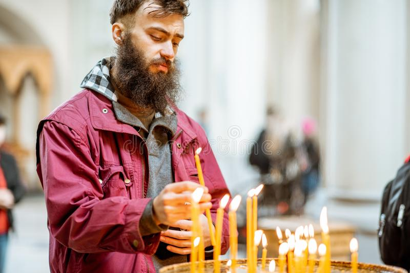 Man putting candles in the church. Bearded man putting candles while praying in the church royalty free stock images