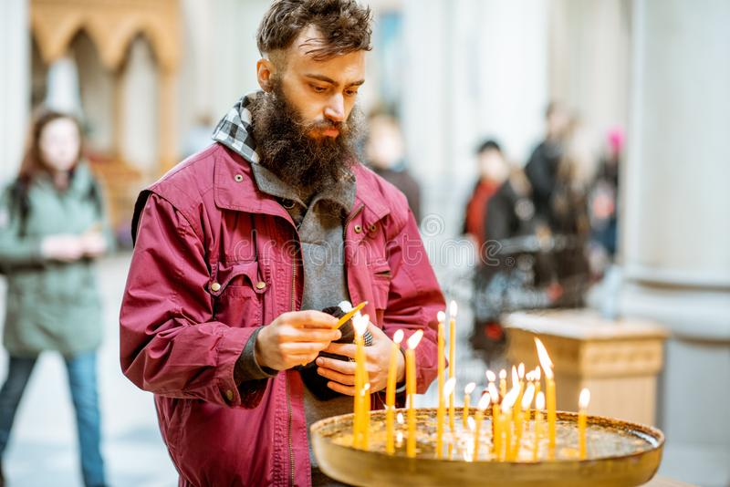 Man putting candles in the church. Bearded man putting candles while praying in the church royalty free stock photo
