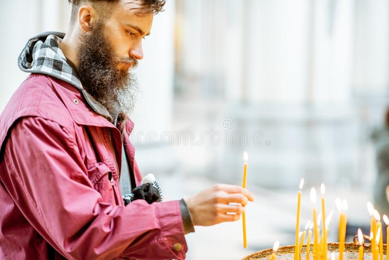 Man putting candles in the church. Bearded man putting candles while praying in the church royalty free stock photography