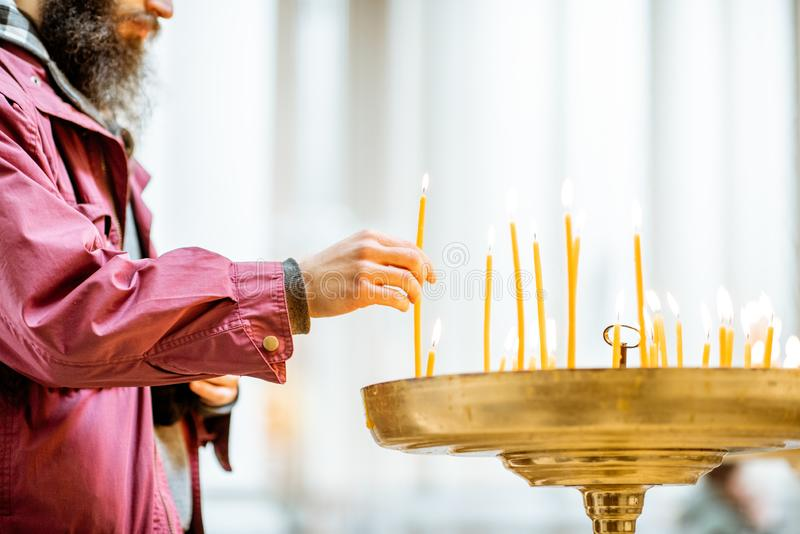 Man putting candles in the church. Man putting candles while praying in the church, close-up view focused on the hand stock photos