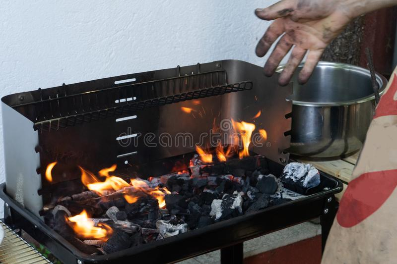 Man putting coal in a Garden Barbeque with fire getting ready to cook meat for a home party. Flame in bbq. Hot Charcoal and wood. Male Hand adding combustible stock photography