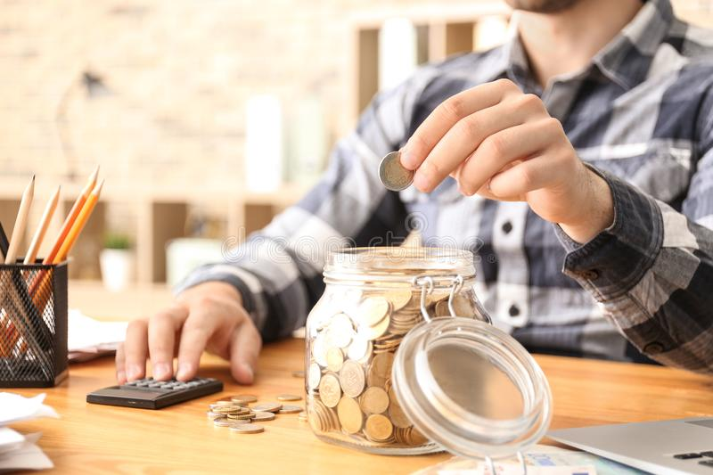 Man putting coin into glass jar indoors. Money savings concept royalty free stock photo