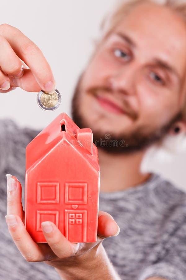 Man putting coin into house piggybank stock photography