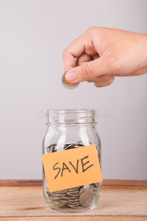 Man Putting Coin Into Jar Labelled Savings. Man Putting Coin Into Jar,save money concept royalty free stock image