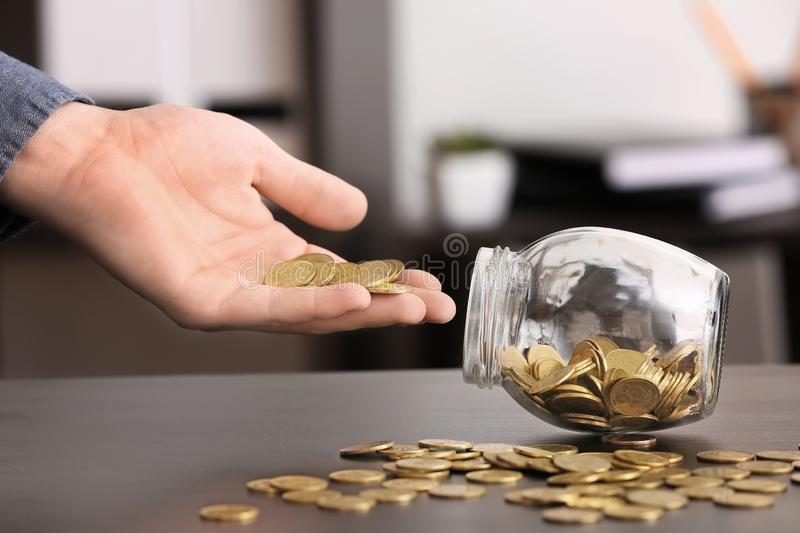 Man putting coins into glass jar on table. Savings concept royalty free stock photos